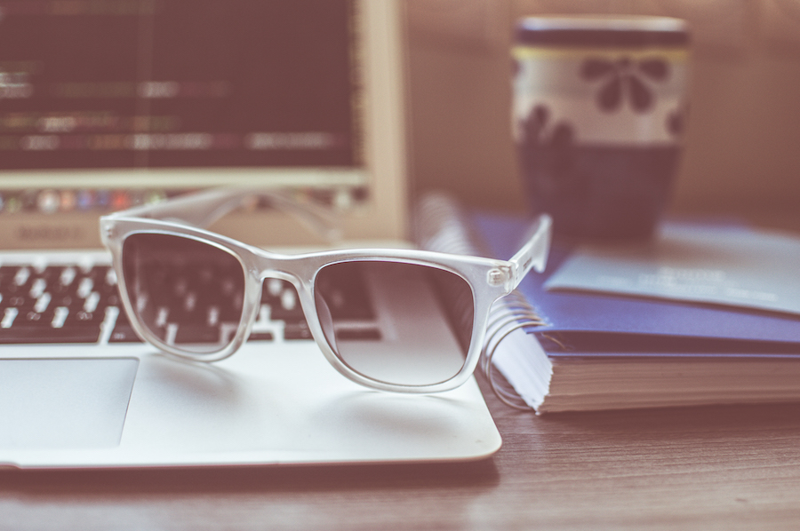 Sunglasses on desk by Caio Resende
